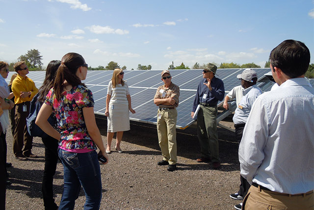 people talking in front of a solar field