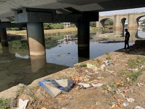 Mutha river with trash on the banks