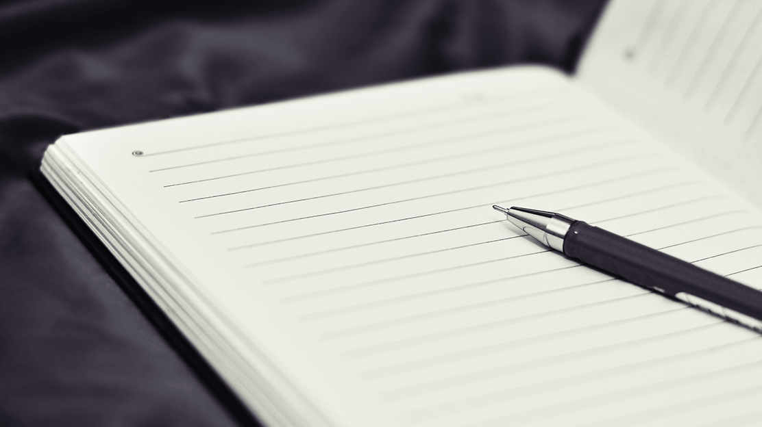 open notebook with pen lying on top
