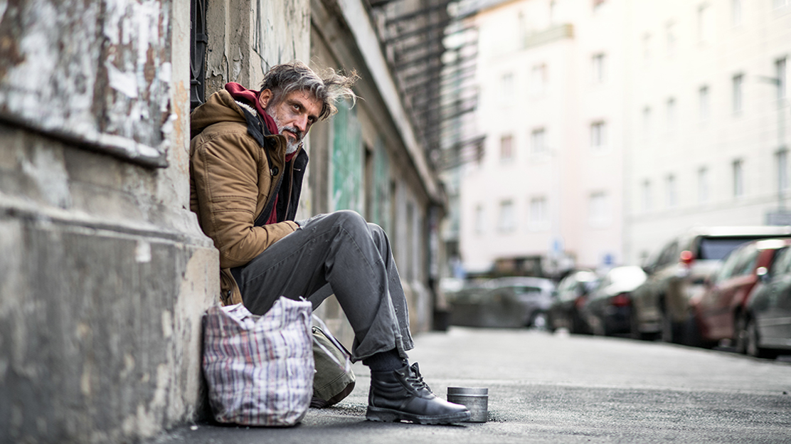 image of a homeless person sitting on the side of a building